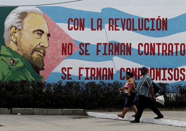 Gente caminando frente a un graffiti del fallecido presidente cubano Fidel Castro en Santiago de Cuba, Cuba 3 de diciembre de 2016.