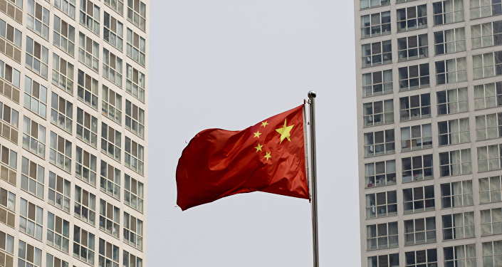 A Chinese national flag flutters in the wind in between a high-rise residential and office complex in Beijing, China. (File)
