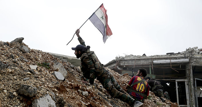Militar sirio emplaza la bandera nacional de Siria