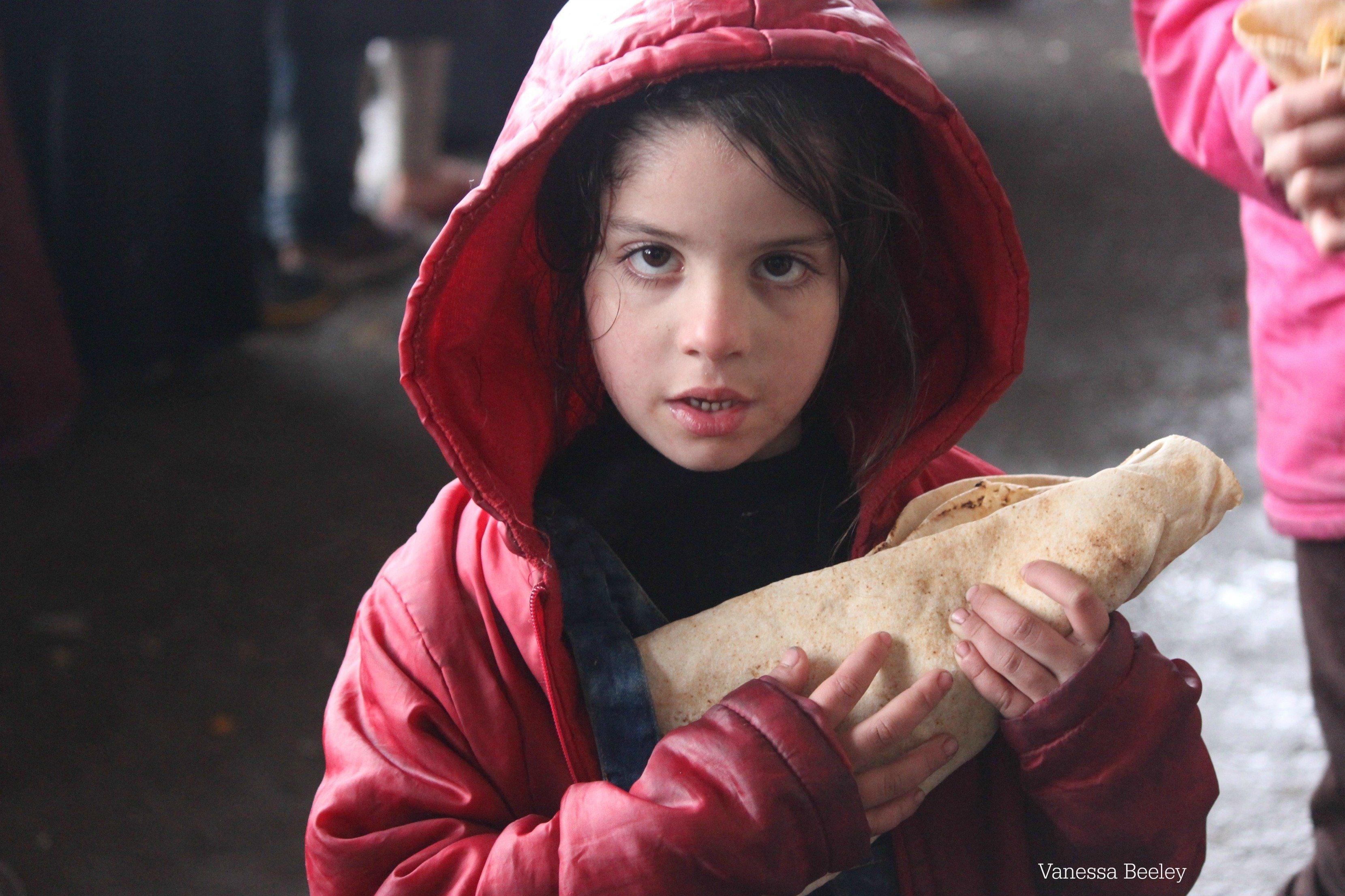 Niños reciben comida en el este de Alepo.