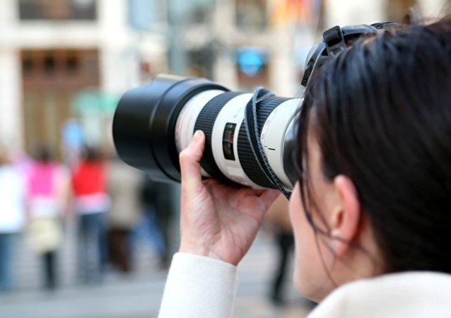 Una mujer con cámara (imagen referencial)