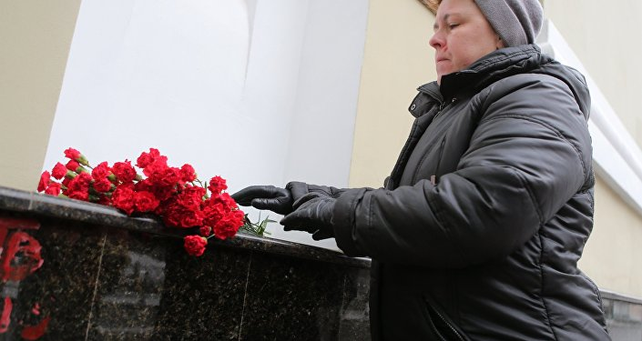Una mujer deposita flores para rendir homenaje a las víctimas de la catástrofe del avión Tu-154
