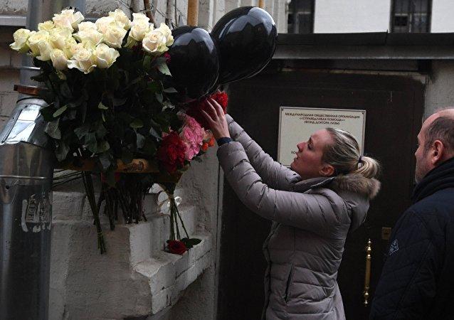 Una mujer deposita flores frente a la sede de la fundación benéfica Ayuda Justa