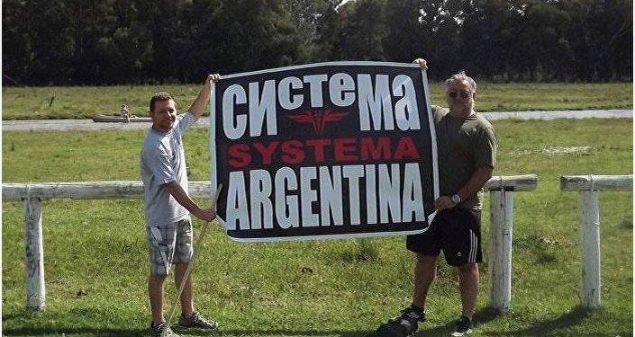 Personas sostienen un cartel de Systema Argentina