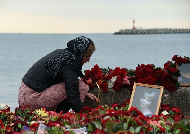 Una mujer lleva flores en memoria de las víctimas del siniestro del Tu-154