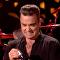 Robbie Williams se desinfecta las manos después de tocar a sus fans