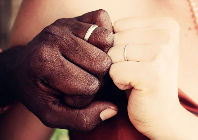 Las manos de una pareja multirracial