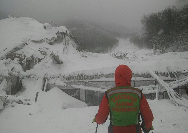 Un socorrista enfrente del hotel destruido por avalancha, Italia