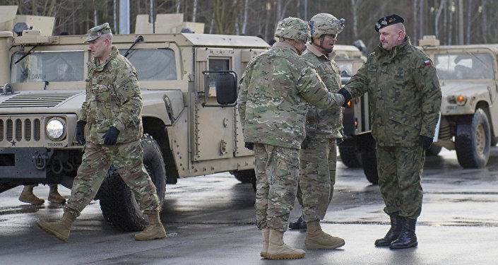 El coronel estadounidense Christopher Norrie y el general polaco Jaroslaw Mika se estrechan la mano durante una ceremonia de bienvenida en la frontera entre Polonia y Alemania