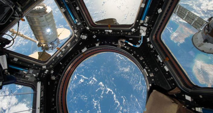 Nave espacial Cugnus visto desde la ventana de un módulo de la EEI