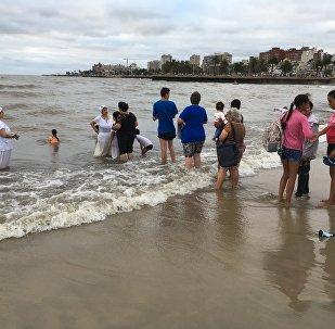 Personas hacen fila para recibir la curación de una mae durante la Fiesta de Yemayá en Montevideo