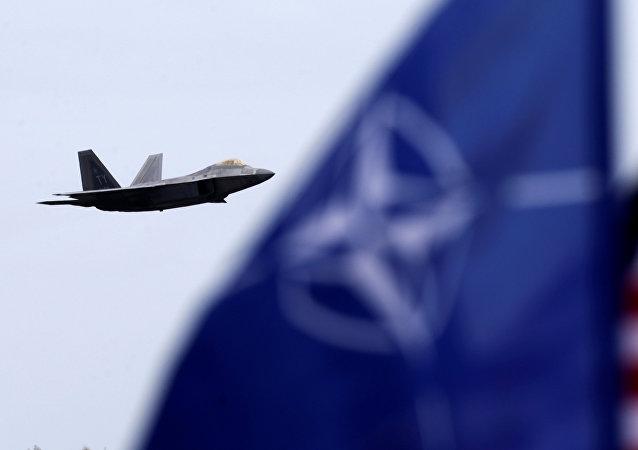 Caza estadounidense F-22 raptor y las banderas de la OTAN y EEUU (archivo)