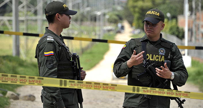 Policemen stand guard at a cordoned-off police station and a power substation where a police officer was killed and his body booby-trapped, in northern Bogota, on December 29, 2016. Colombia accused the ELN rebels Thursday of killing a Bogota policeman, then hiding explosives by his body and detonating them when colleagues rushed to his side, wounding five.