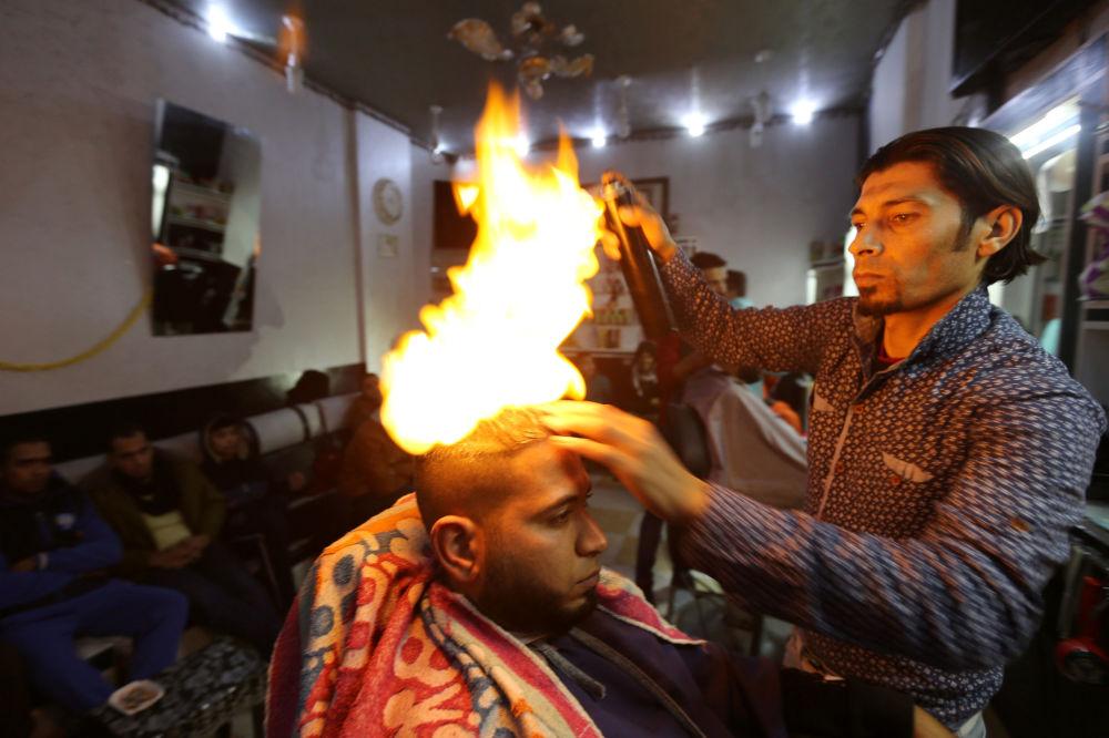 El peluquero palestino Ramadan Edvan alisa el pelo de un cliente con fuego en una barbería en Rafah, en el sur de la Franja de Gaza