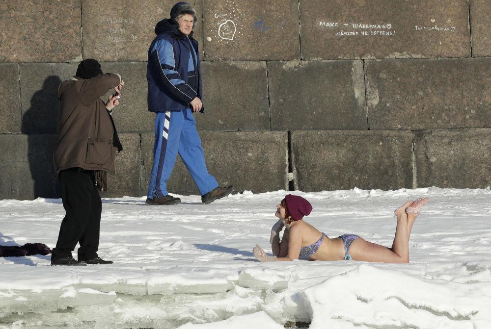 Un hombre hace una foto a una mujer que toma el sol sobre la nieve cerca de los muros de la Fortaleza de San Pedro y San Pablo en San Petersburgo. La temperatura en aquel momento era de -12oC