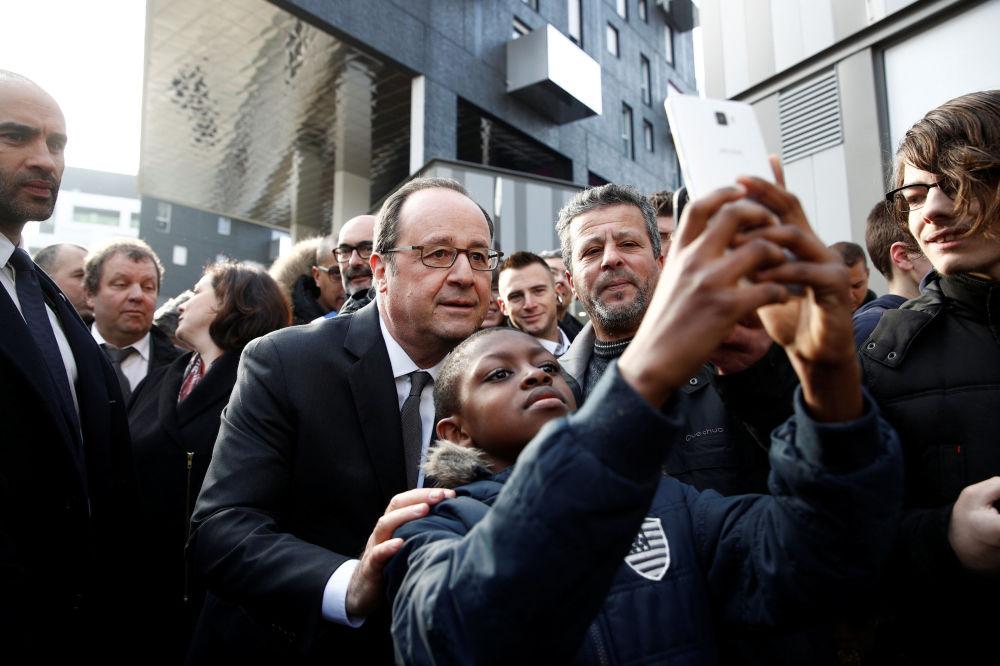 El mandatario francés, François Hollande, se fotografía con un niño en los suburbios de París