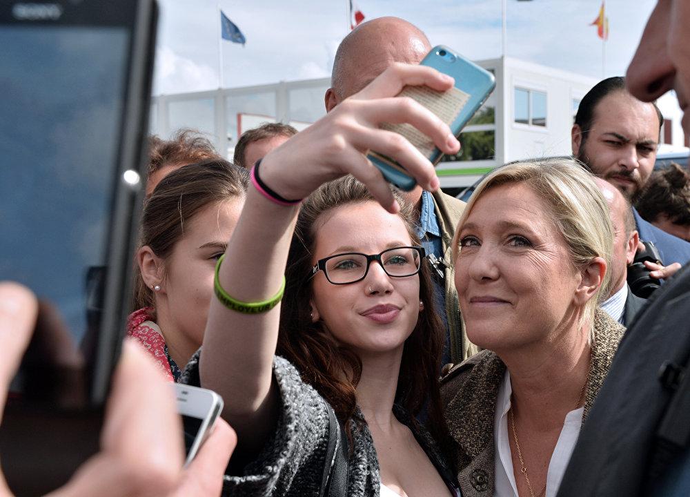 La líder del Frente Nacional, Marine Le Pen, posa con una visitante en la Exposición Internacional de Ganadería en Francia