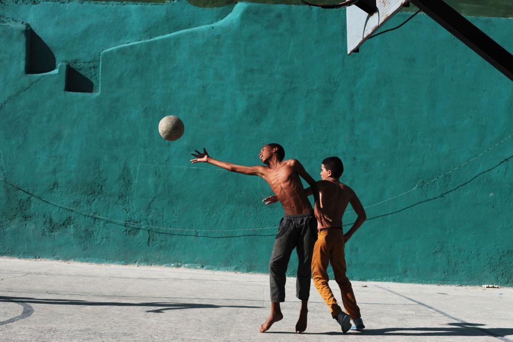 Chicos jugan al baloncesto en la zona residencial de La Habana Vieja