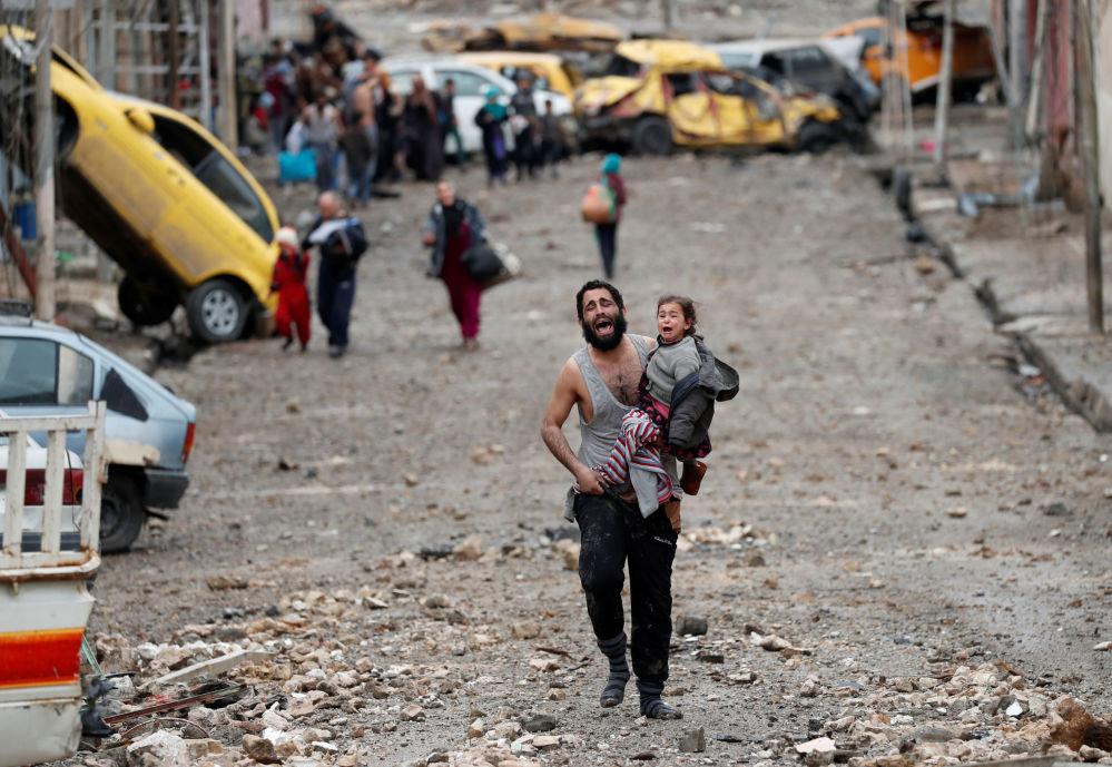Un padre lleva a su hija en brazos mientras huyen desde los territorios controlados por los yihadistas de Daesh durante la batalla de Mosul