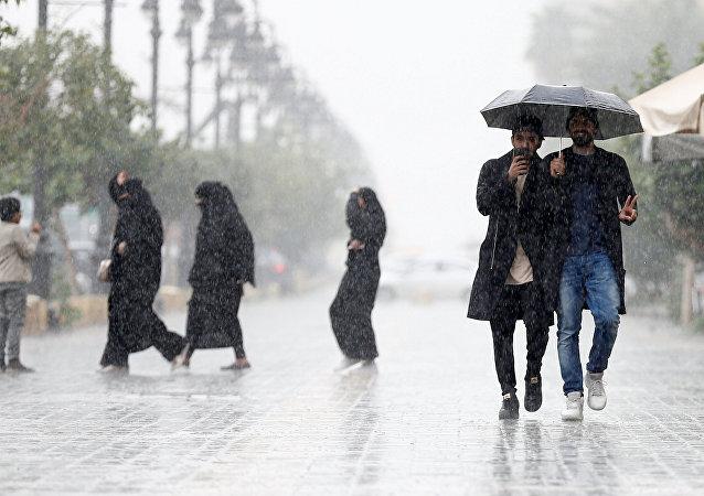La gente bajo la lluvia en una calle de Riad
