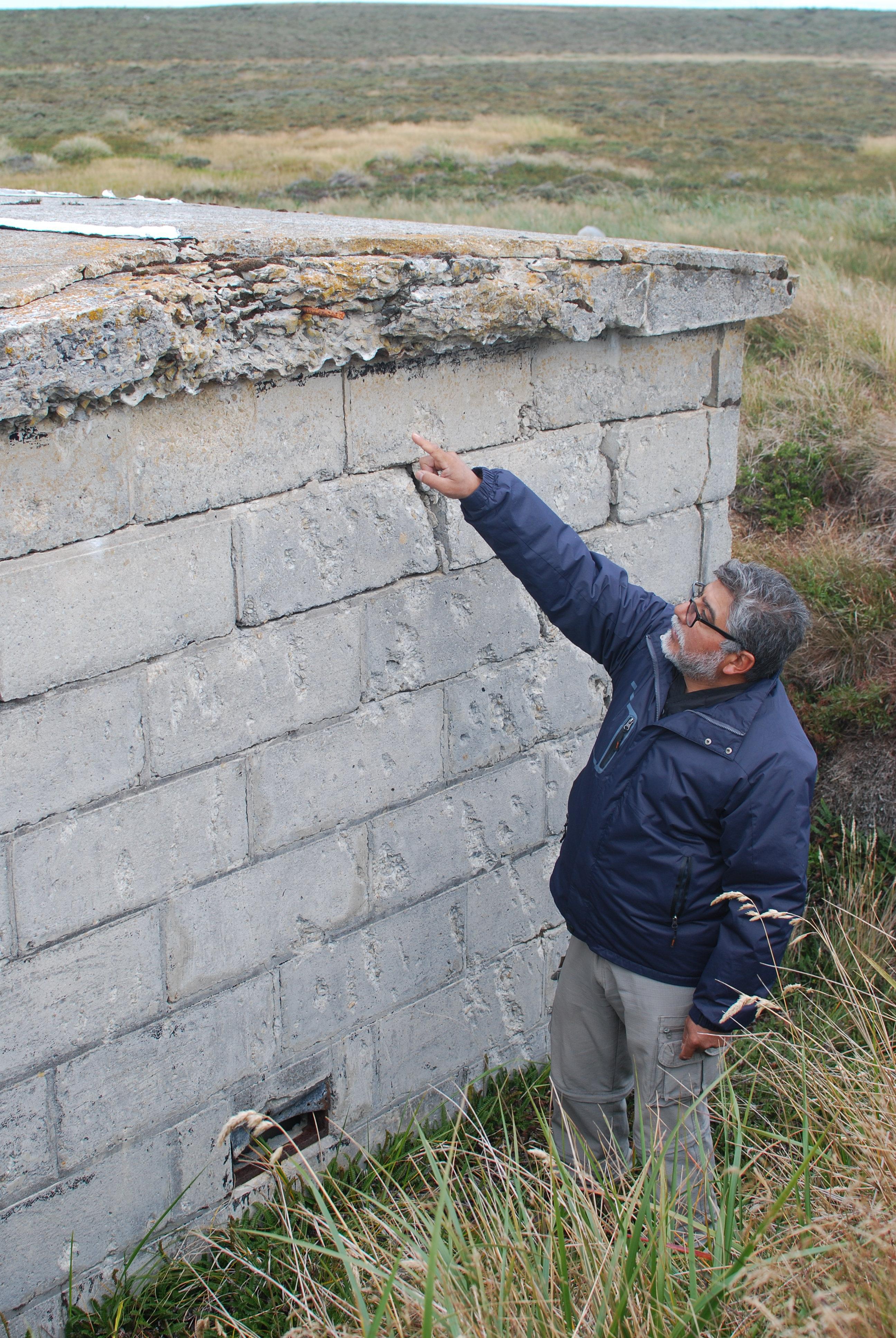 El excombatiente Armando González muestra daños de un proyectil en un refugio donde permaneció algunos días durante la Guerra de Malvinas