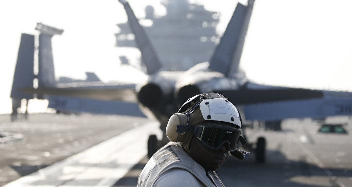 Un miembro de la tripulación de la Marina estadounidense al lado del caza F / A-18 Super Hornet que se prepara para despegar del USS Ronald Reagan, portaaviones de la clase Nimitz de propulsión nuclear