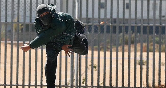 Manifesante tira piedras contra los policías durante el Día del Joven Combatiente en Chile