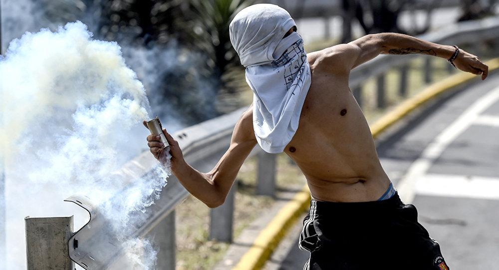 Un hombre lanza gas lacrimógeno, Caracas, Venezuela (archivo)