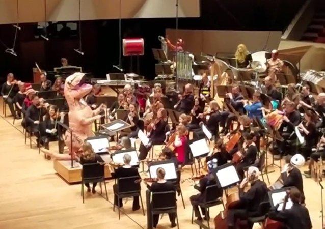 Cristopher Dragon, disfrazado de dinosaurio, dirige a su orquesta