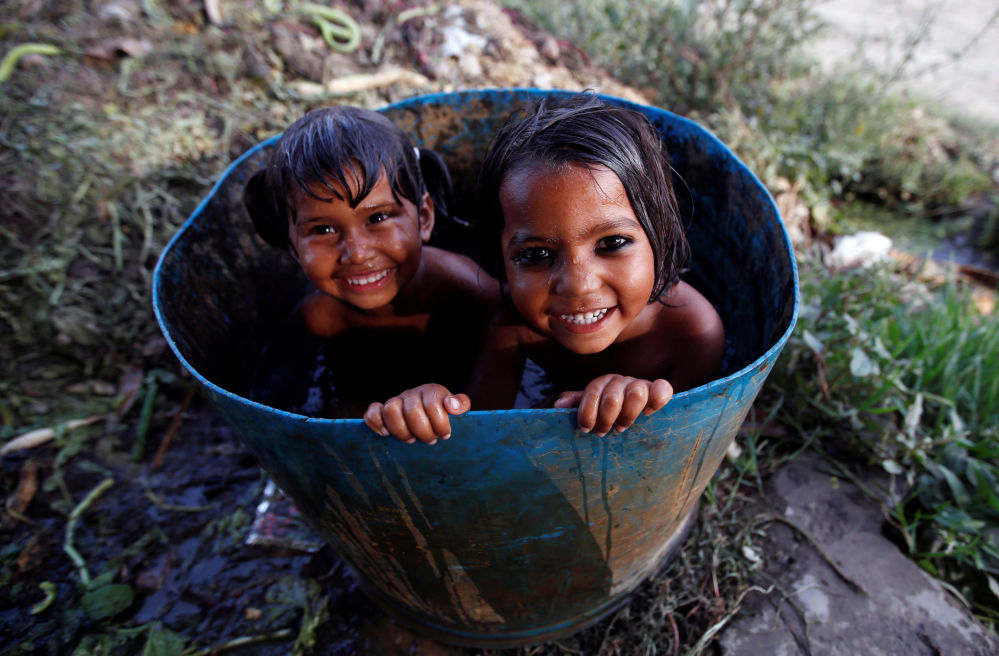 Niñas se bañan en un tambor roto en Nueva Delhi, La India