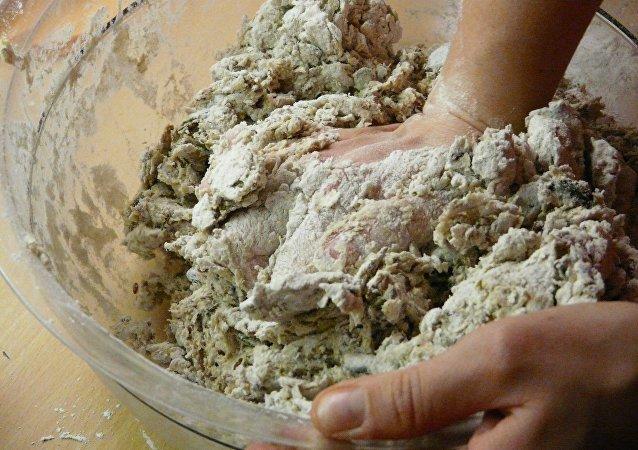 Una mano prepara una masa de pan