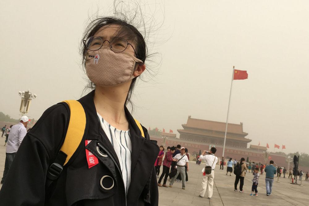Transeúntes en la plaza de Tiananmen en Pekín durante una tormenta de polvo.