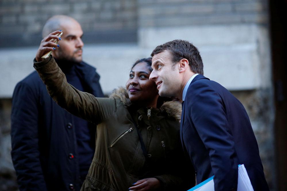El candidato presidencial francés, líder del movimiento 'Adelante', Emmanuel Macron se fotografía con los votantes junto a su casa en París.