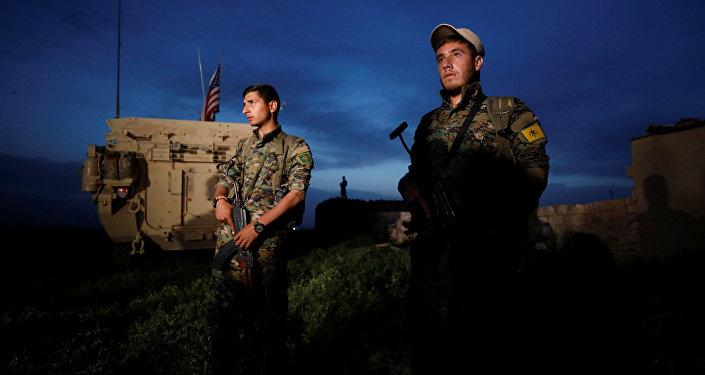 Los kurdos de YPG cerca del vehículo militar de EEUU