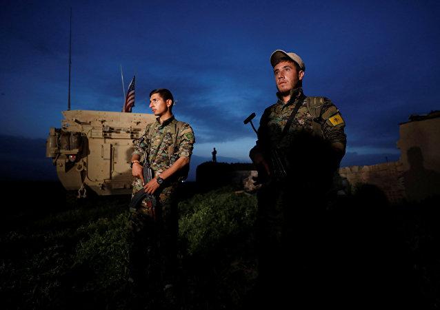 Los kurdos de YPG cerca del vehículo militar de EEUU (archivo)