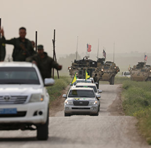 Fuerzas de autodefensa kurdas a bordo de un convoy de vehículos estadounidenses