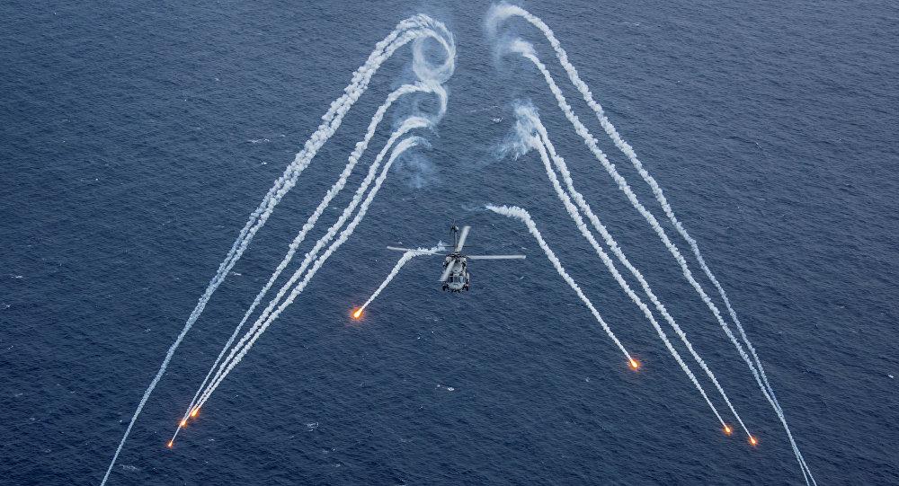 Un helicóptero de la Marina de guerra de EEUU echa bengalas durante un ejercicio de entrenamiento