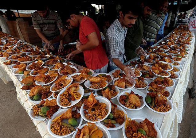 Unas personas organizan platos de comida para que los transeúntes interrumpan su ayuno durante un mes de Ramadán en Karachi