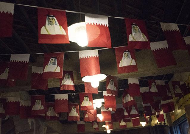 Banderas de Catar con la imagen del emir Tamim bin Hamad Thani