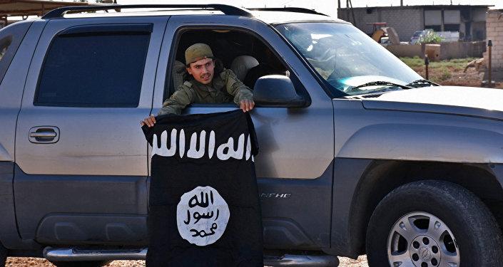 Un combatiente pro-gubernamental sirio demuestra la bandera de Daesh sacada de una aldea liberada
