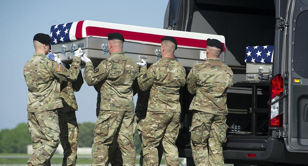 Un equipo de transporte del Ejército de EEUU coloca una caja que contiene los restos de su colega