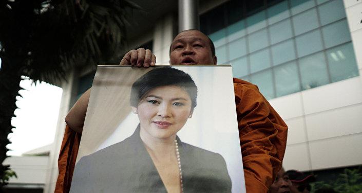 Un monje con la foto de la ex primera ministra de Tailandia, Yingluck Shinawatra
