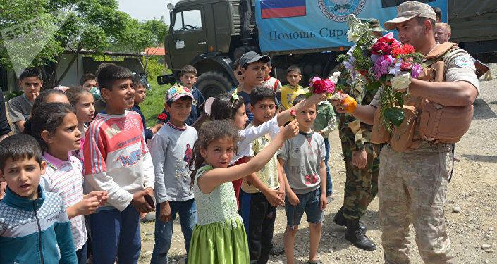 Los habitantes de una aldea siria saludan la ayuda humanitaria llevada por los militares rusos