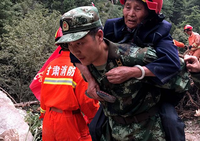 Un rescatista socorre a una mujer afectada por el terremoto en China