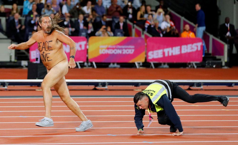 Un guardia persigue a un hombre desnudo que se coló en la pista durante el Campeonato Mundial de Atletismo de 2017