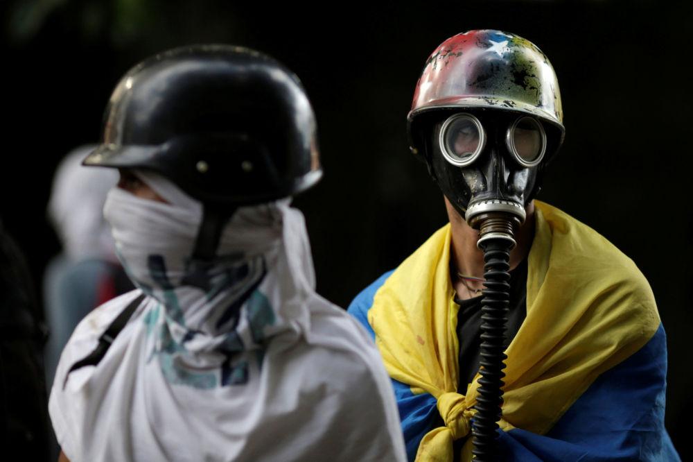 Los manifestantes lucen máscaras antigás en Caracas