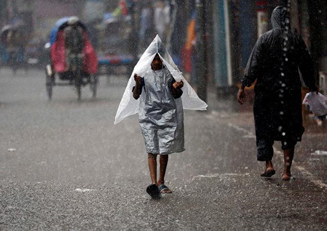 Un chico bajo la lluvia en Bangladés