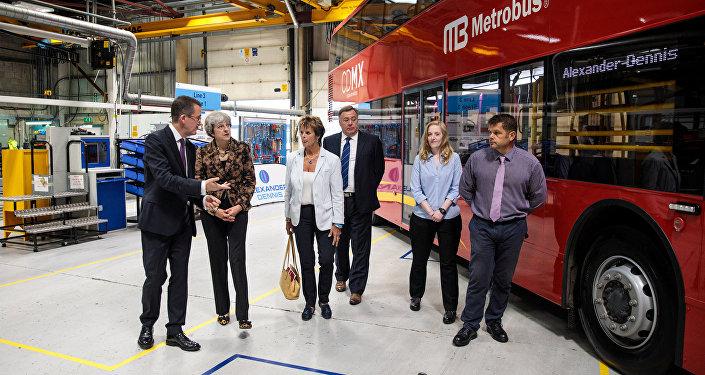 Theresa May, la premera ministra británica cerca del autobús rojo destinado para México