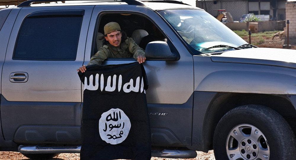 Un combatiente pro-gubernamental sirio demuestra la bandera de Daesh sacada de una aldea liberada (archivo)