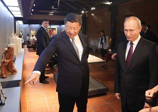 El presidente de Rusia, Vladímir Putin, y su par chino, Xi Jinping, en una exposición de artesanía nacional de China